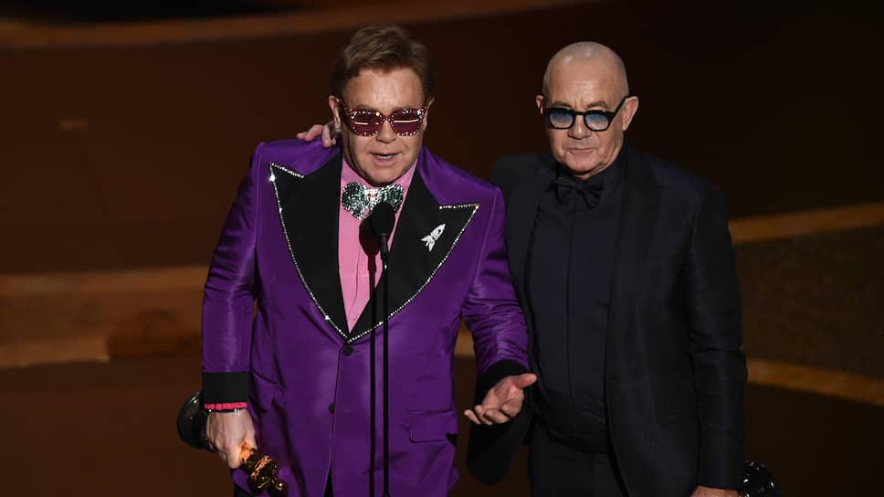 Певец и композитор Элтон Джон (слева) и поэт-песенник Берни Топин получают «Оскар» в номинации «Лучшая песня»