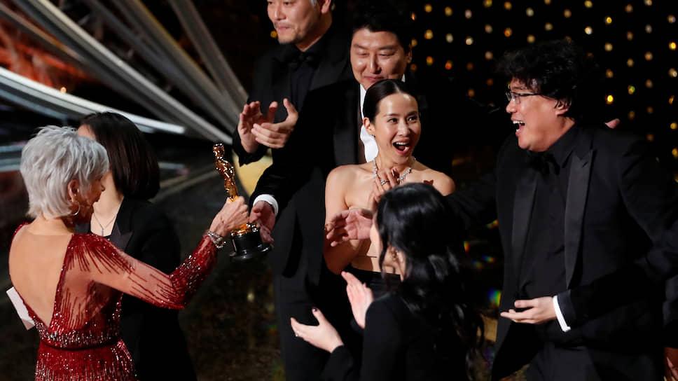 Режиссер Пон Чун Хо (справа) со съемочной группой фильма «Паразиты» получают «Оскар» из рук актрисы Джейн Фонды