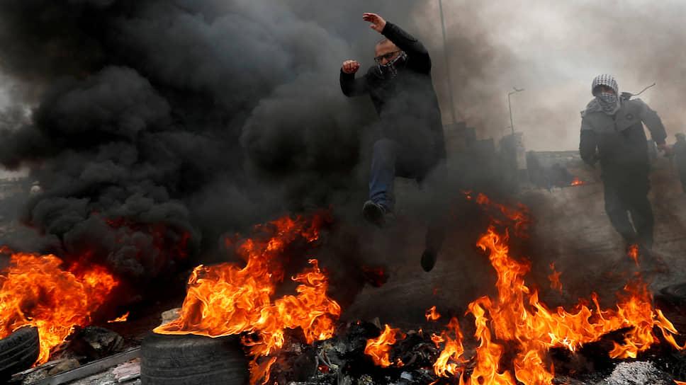 Бейт-Эль, Западный берег реки Иордан. Палестинец перепрыгивает через горящие шины во время акции протеста