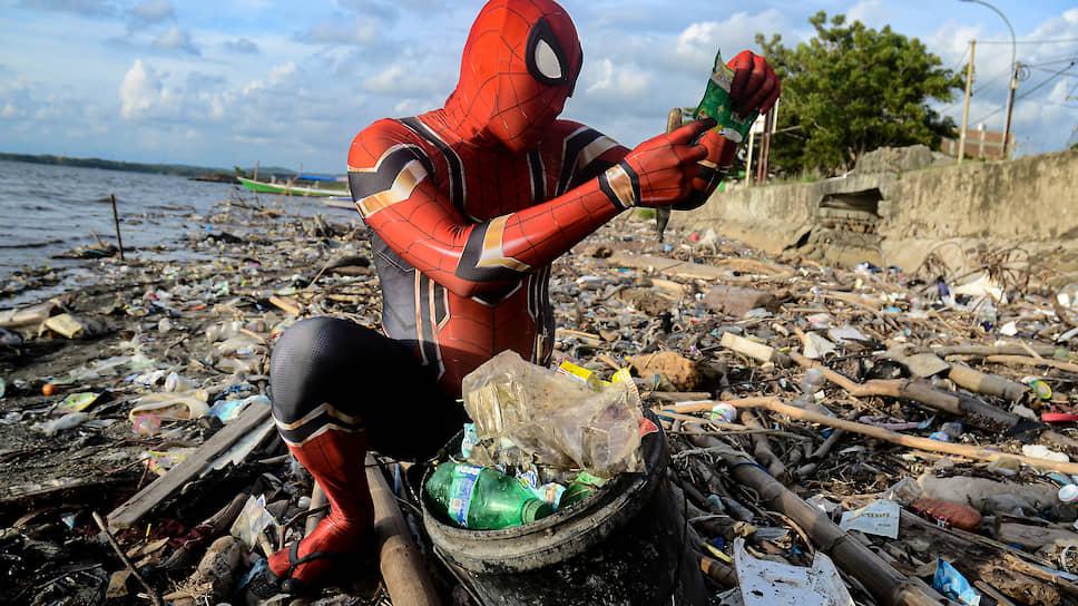Паре-Паре, Индонезия. Мужчина в костюме Человека-паука собирает мусор на пляже