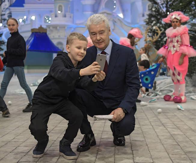 Мэр Москвы Сергей Собянин фотографируется с одним из первых посетителем парка