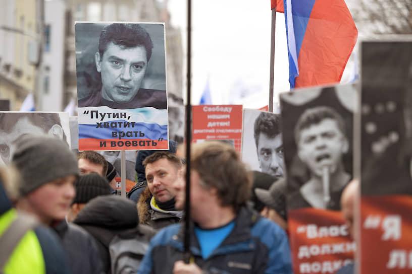 Участники марша памяти Бориса Немцова в Москве несут плакаты с цитатами политика
