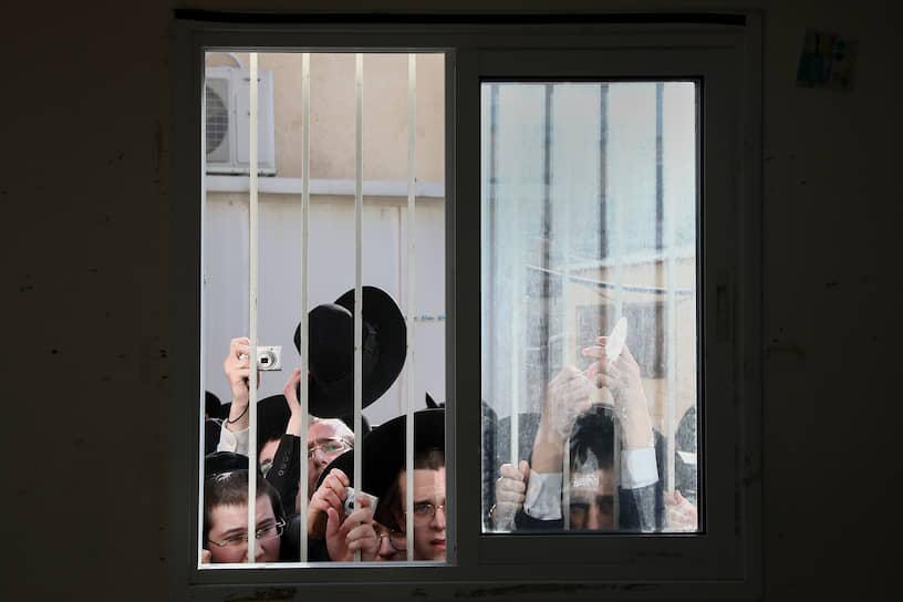 Бней-Брак, Израиль. Ультраортодоксальные евреи наблюдают за тем, как раввин голосует на избирательном участке
