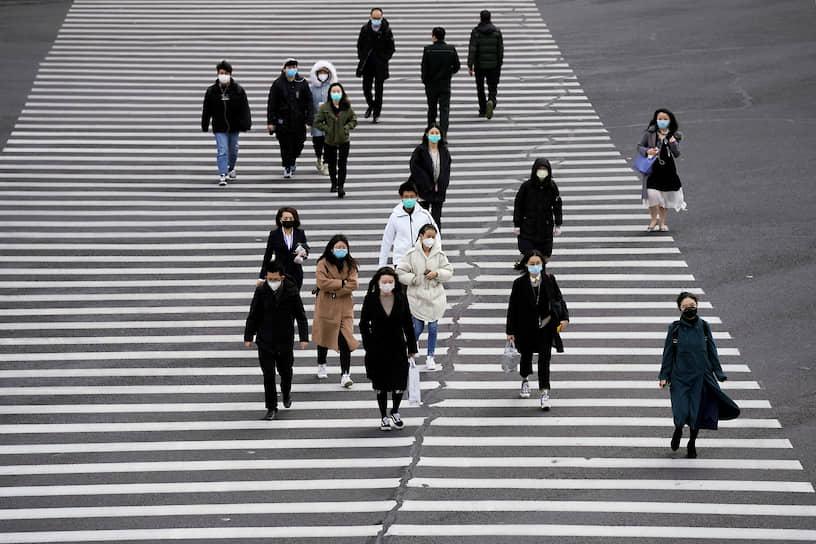 Шанхай, Китай. Люди в медицинских масках переходят через дорогу