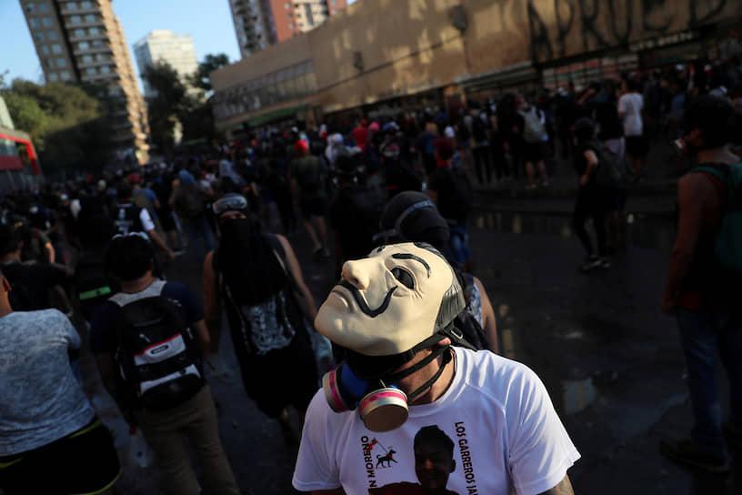 Сантьяго, Чили. Демонстрант в маске на акции протеста против повышения цен в стране