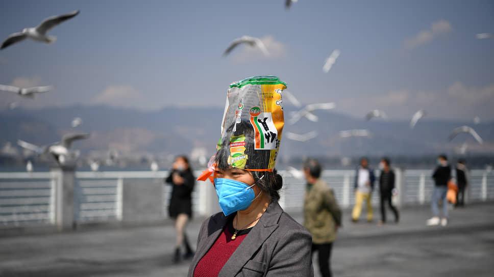 Провинция Юньнань, Китай. Женщина в маске с пакетом на голове для защиты от коронавируса