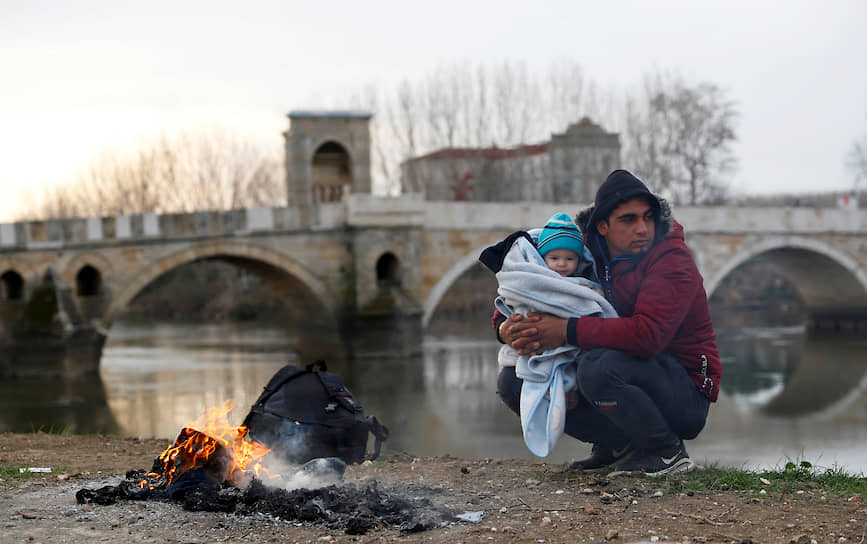 Эдирне, Турция. Мигрант с ребенком на руках у реки на границе с Грецией