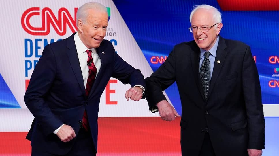 Бывший вице-президент США Джо Байден (слева) и сенатор от штата Вермонт Берни Сандерс изменили этикет приветствий из-за коронавируса