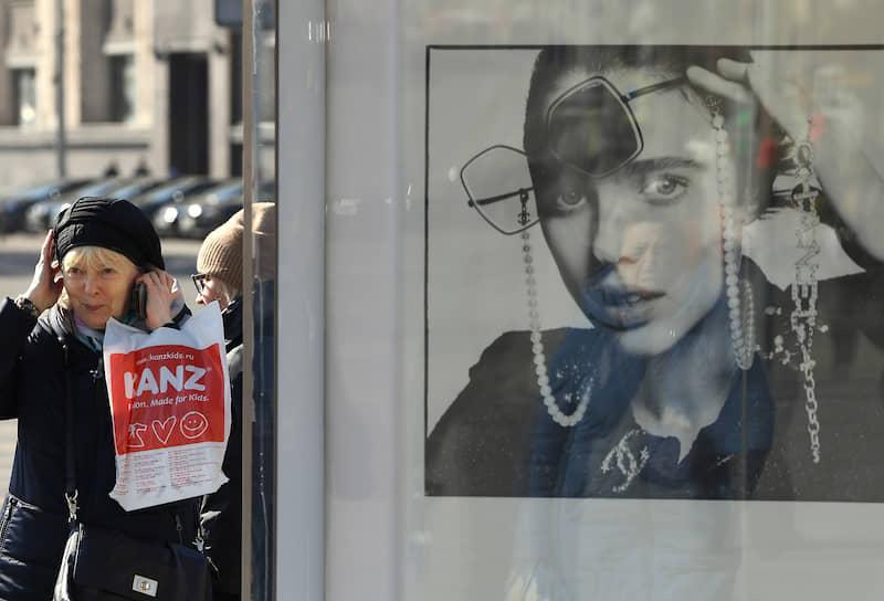 Москва, Россия. Женщина у рекламного щита