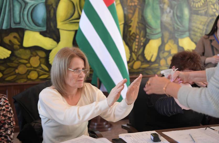 Члены участковой избирательной комиссии обрабатывают руки антисептиком в качестве защиты от коронавирусной инфекции
