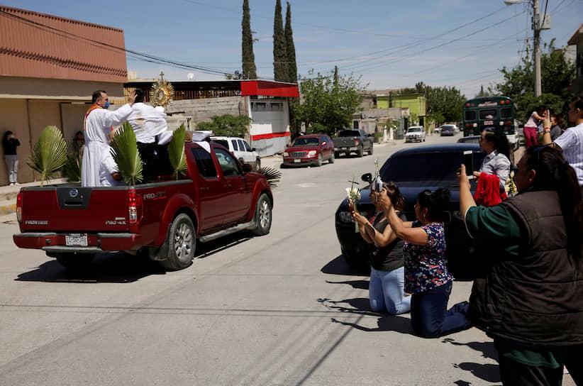 Сьюдад-Хуарес, Мексика. Священник благословляет людей, собравшихся на улицах городах