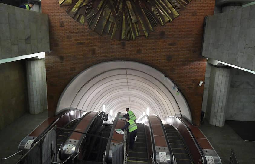 Сотрудники метрополитена моют эскалатор на станции «Боровицкая» Московского метрополитена