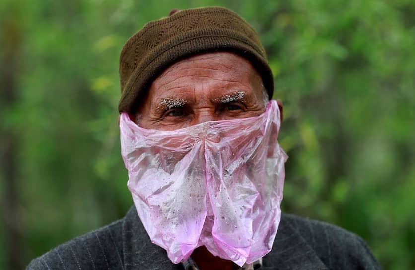 Сринагар, Индия. Мужчина прикрывает лицо пластиковым пакетом вместо медицинской маски