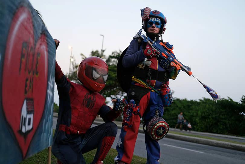 Рио-де-Жанейро, Бразилия. Мужчины в костюмах Человека-паука и Капитана Америки возле плаката с надписью «Оставайтесь дома»