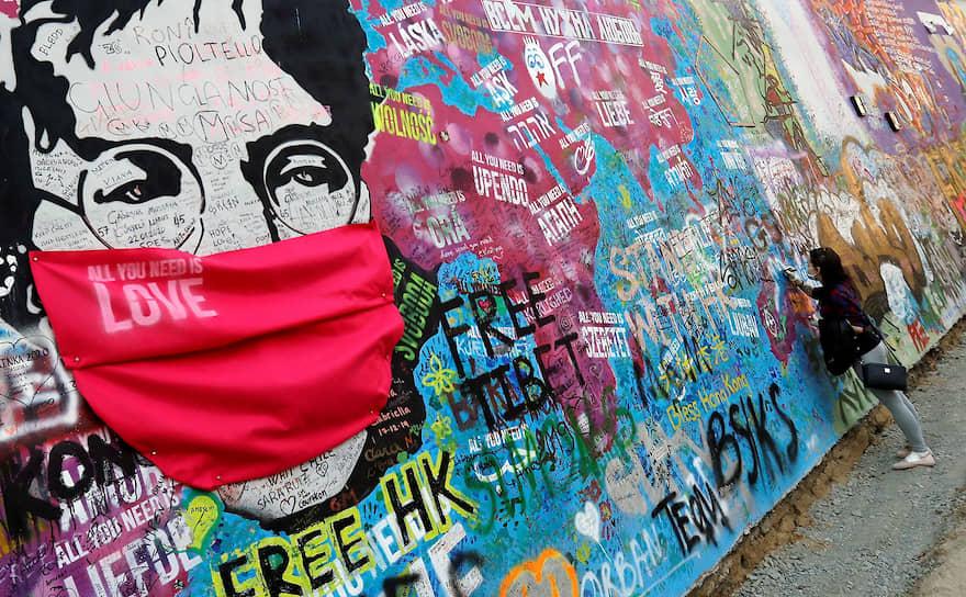 Прага, Чехия. Девушка расписывается на стене, посвященной Джону Леннону