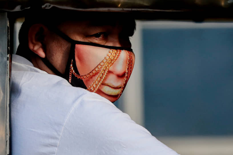 Кесон-Сити, Филиппины. Водитель джипа в маске с изображением лица