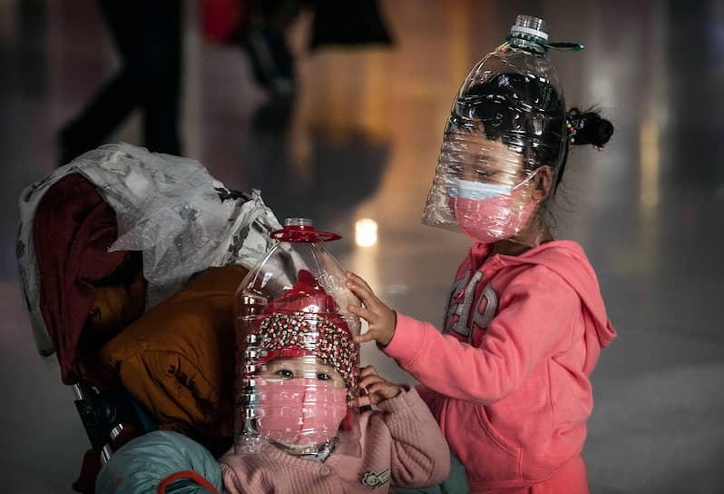 Пекин, Китай. Дети в защитных масках из пластиковых бутылок ждут вылета в аэропорту