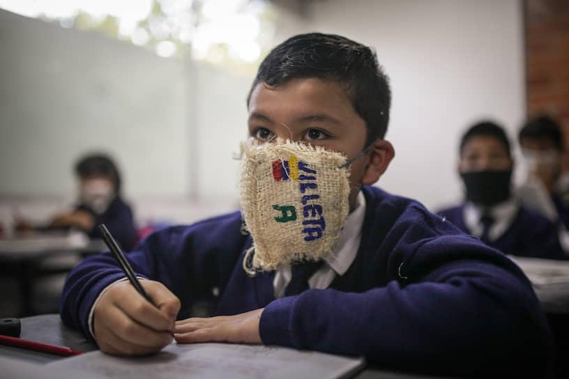 Соача, Колумбия. Школьник в самодельной маске. Колумбийцы делают маски из мешковины, использованных стаканчиков, банановых листьев и других подручных материалов, потому что медицинские средства защиты слишком дороги