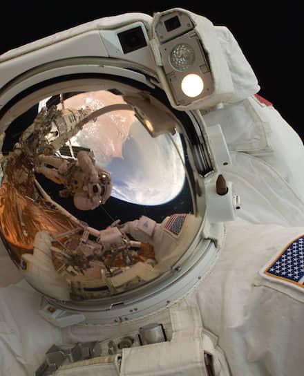 Астронавты Джон Грюнсфелд и Эндрю Фейстел (в отражении) в открытом космосе во время технического обслуживания космического телескопа Hubble