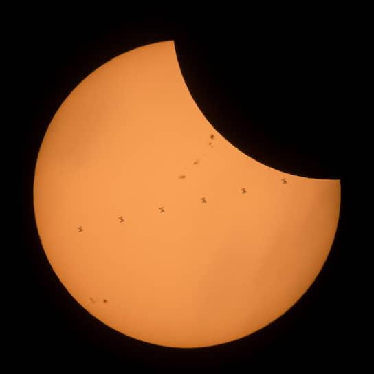 Композитное изображение, сделанное из нескольких кадров. Международная космическая станция (МКС) проходит по диску Солнца во время частичного затмения