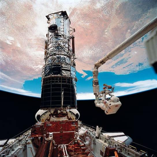 Астронавты в открытом космосе во время технического обслуживания космического телескопа Hubble