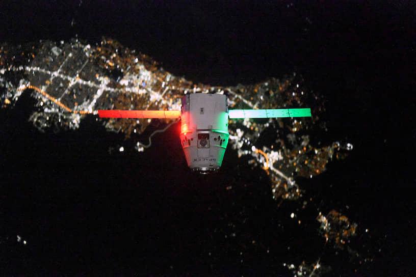 Грузовой космический корабль Dragon подлетает к МКС на фоне ночного города. Он является единственным в мире грузовым кораблем, возвращающим грузы с МКС на Землю
