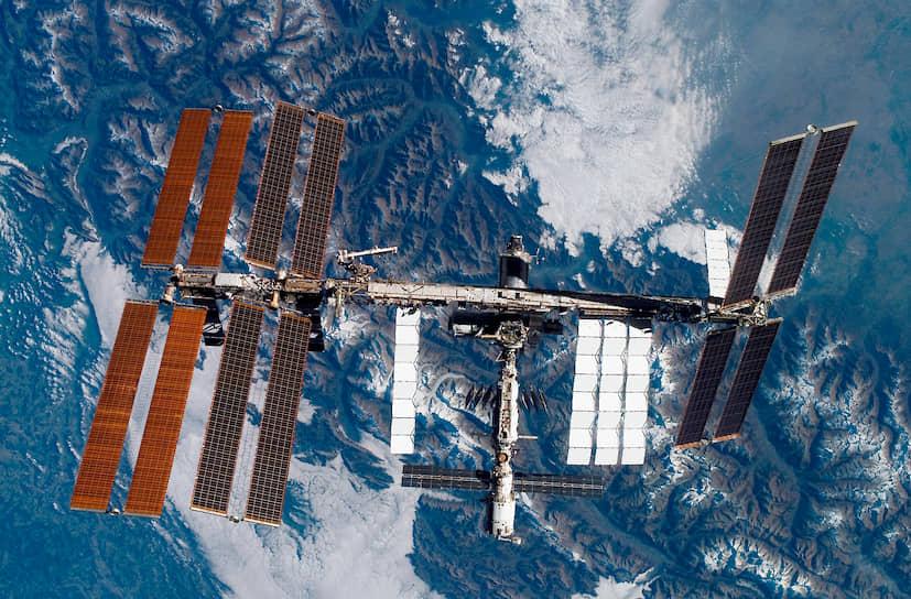 Вид на Международную космическую станции с шаттла Discovery. Параметры станции: длина  51 м, ширина вместе с фермами — 109 м, высота — 20 м, вес — 417,3 тонны