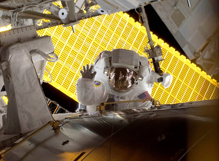 Астронавт Николь Стотт во время выхода в открытый космос на фоне солнечных панелей Международной космической станции