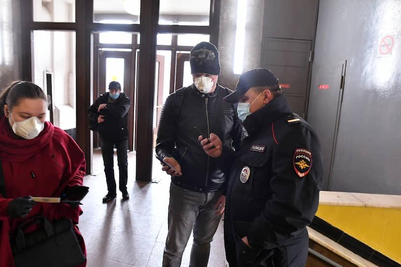 Пассажир метро показывает код своего электронного пропуска на экране смартфона сотруднику полиции на станции метро «Сокольники»