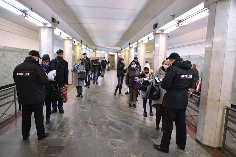 Пассажиры метро показывают электронные пропуска сотрудникам полиции на станции метро «Сокольники»
