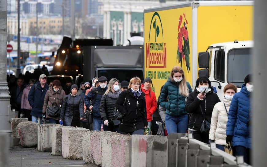 Люди идут вдоль автомобильной пробки на въезде в Москву
