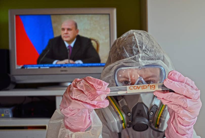 Ребенок в защитном костюме с пробиркой на фоне трансляции выступления премьер-министра Михаила Мишустина