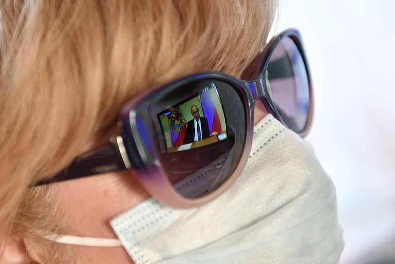 Женщина в маске смотрит трансляцию телеобращения Владимира Путина