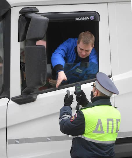 Сотрудник ДПС проверяет у водителя пропуск при въезде в Москву на Ленинградском шоссе