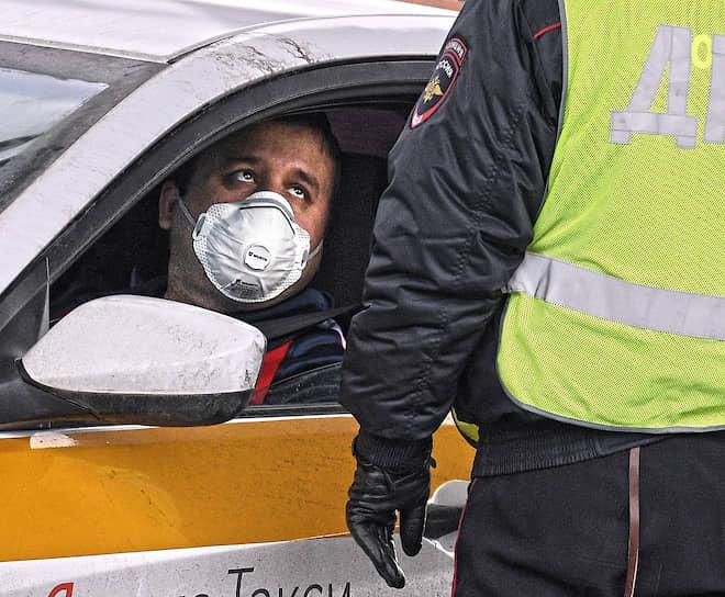 Москва. Сотрудник ДПС во время проверки у водителя пропуска для въезда в город на Варшавском шоссе