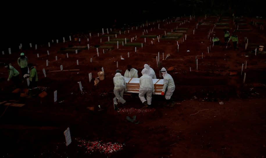 Джакарта, Индонезия. Работники муниципальной службы несут гроб на кладбище для жертв коронавируса