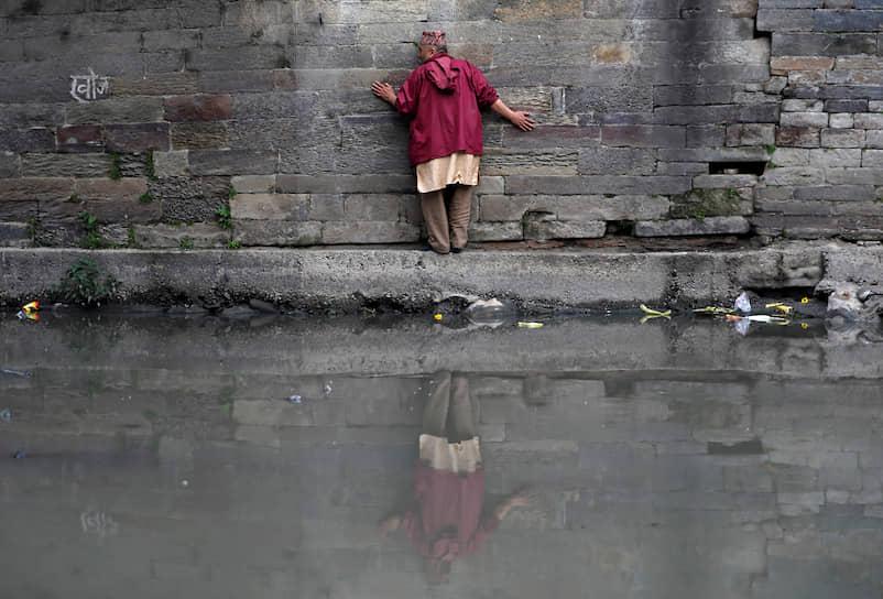 Катманду, Непал. Мужчина пытается пройти вдоль стены у реки