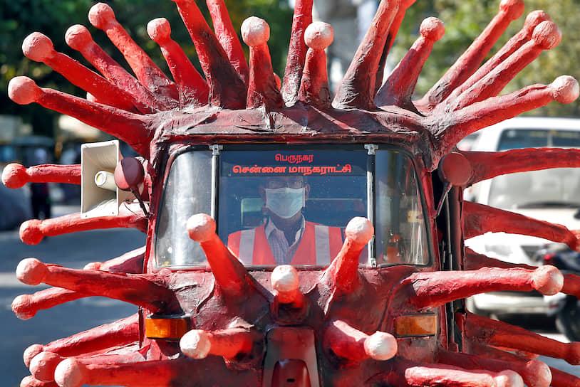 Ченнаи, Индия. Мужчина за рулем моторикши в виде коронавируса