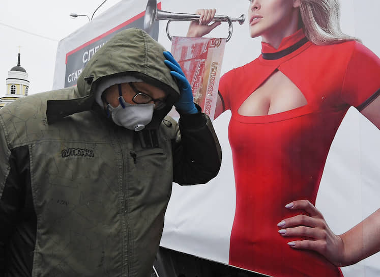 18 апреля. Москва. Мужчина на фоне рекламного плаката