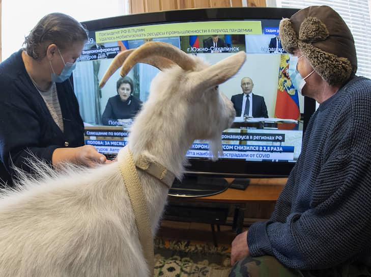 28 апреля. Москва. Люди смотрят выступление президента России Владимира Путина перед совещанием с главами регионов