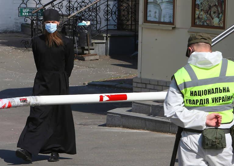28 апреля. Киев, Украина. Священнослужитель в медицинской маске перед входом в Киево-Печерскую Лавру