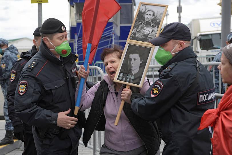 Женщина с портретами участников войны в центре Москвы. Официально акция «Бессмертный полк» в этом году перенесена на неопределенное время