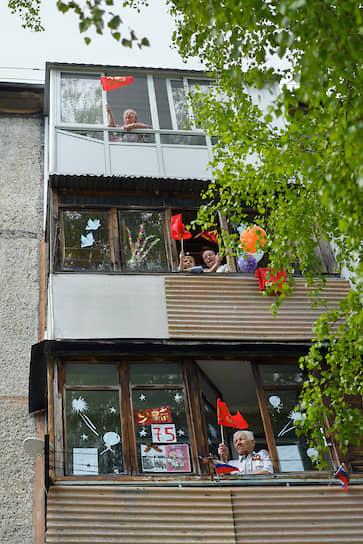 Жители Кемерово с балконов приветствуют мини-парад губернатора региона Сергея Цивилева под окнами ветерана Великой Отечественной войны Валентины Крамаренко