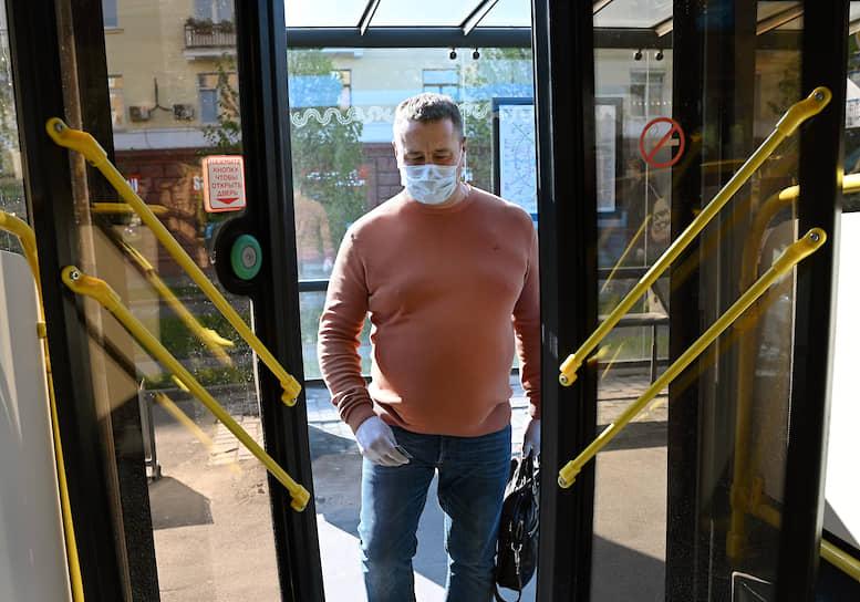 Мужчина в маске и резиновых перчатках на входе в автобус