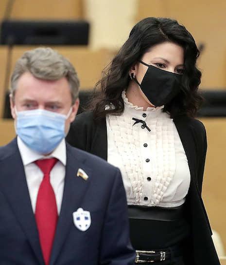 Некоторые депутаты Госдумы приходят на заседания со значками в виде белого креста на черном фоне. Такие значки продаются в аптеках как дезинфицирующее средство, которое «очищает пространство вокруг человека», защищает от гриппа и других вирусов. <br> На фото: депутаты Инга Юмашева и Анатолий Выборный