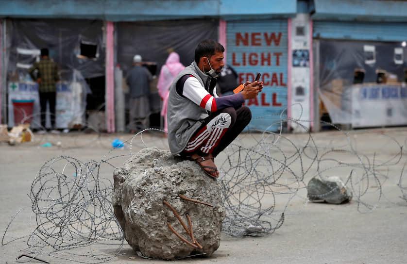 Сринагар, Индия. Мужчина сидит на цементном блоке во время общенационального карантина