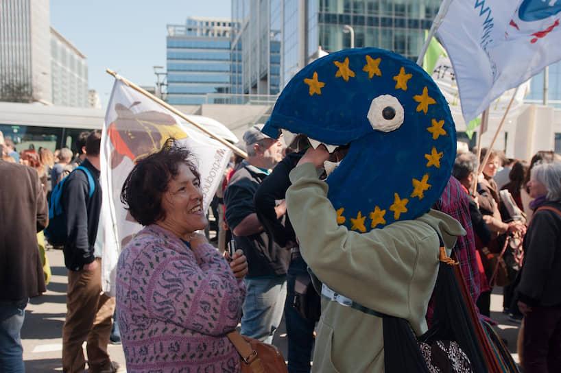 Имя героя игры образовано от японского звукоподражательного выражения «паку-паку», обозначающего открытие и закрытие рта во время еды <br> На фото: участник акции протеста в Брюсселе против договора о Трансатлантическом торговом и инвестиционном партнерстве