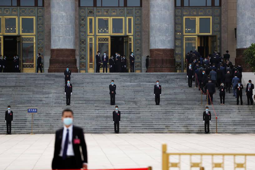 Пекин, Китай. Сотрудники службы безопасности у Дома народных собраний перед началом заседания парламента страны