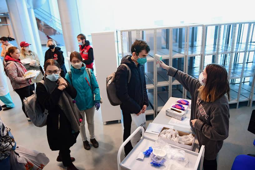 Добровольцы из общественного движения «Волонтеры-медики» готовятся к работе во временном госпитале для зараженных коронавирусом в павильоне выставочного комплекса «Ленэкспо». Павильон был переоборудован к 25 апреля, теперь здесь 1 тыс. койко-мест
