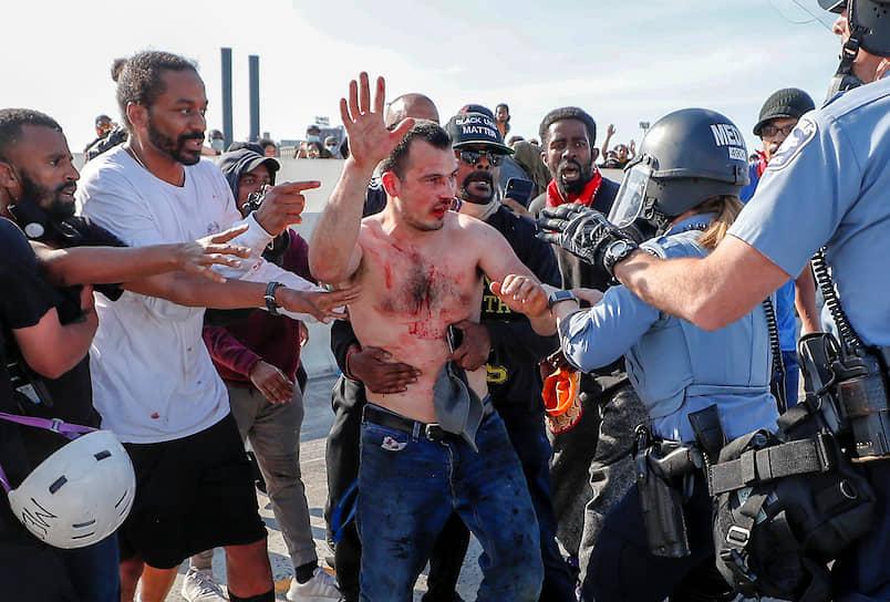На фоне беспорядков Дональд Трамп также заявил в своем Twitter, что США внесут движение «Антифа» в список террористических организаций и возложил ответственность за беспорядки в Миннеаполисе на «радикальных левых анархистов» <br>На фото: протестующие передают полиции водителя автоцистерны, который после наезда на толпу был вытащен из кабины и избит демонстрантами